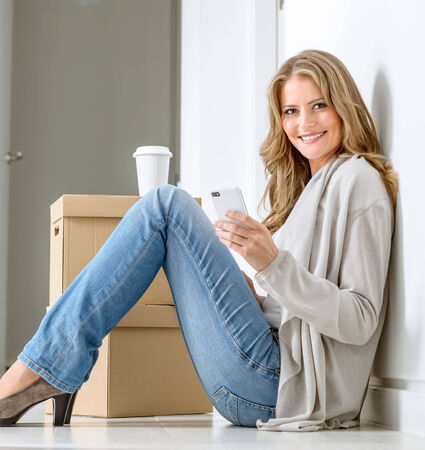 Smiling woman sitting on the floor with a pile of boxes, having a coffee break and texting with her smart phone photo