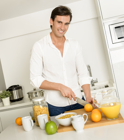 Man in the kitchen cutting oranges for breakfast photo