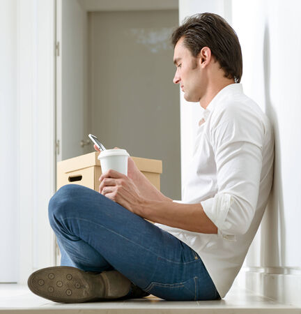 Man, with pile of boxes,  sitting on the floor with a coffee, checking his smart phone photo