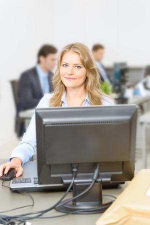 administrador de empresas: Mujer que trabaja en su escritorio, con las personas que trabajan en el fondo Foto de archivo