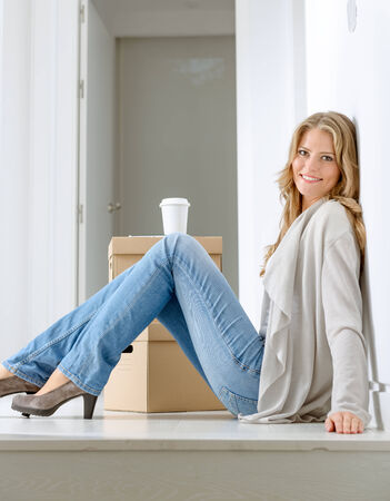 Smiling woman sitting on the floor with a pile of boxes, having a coffee break photo