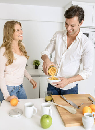 Couple preparing a healthy breakfast with fruit and cereal photo