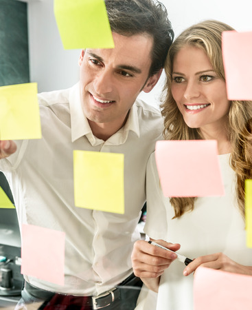 Male and female coworkers standing in front of a glass wall with sticky notes photo