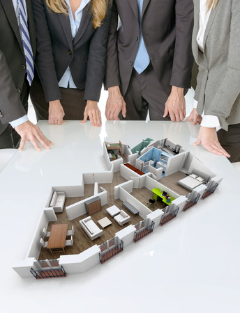 Meeting with people around a table with an architecture model showing an apartment photo