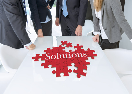 work man: Meeting with people around a table with a puzzle with the words solutions
