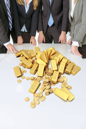 Meeting with people around a table with golden ingots and coins photo