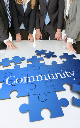 Meeting with people around a table with a puzzle with the word community photo