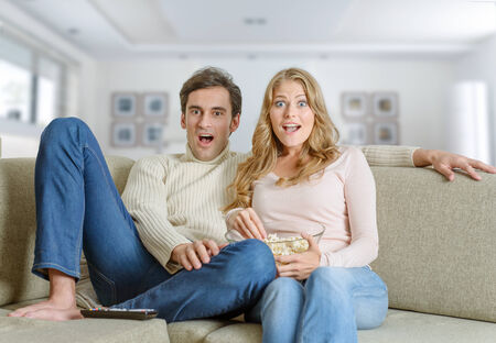 A couple at home watching tv with a surprised expression photo