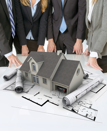 real estate concept: Meeting with people around a table with an architectural model on top of documents and charts