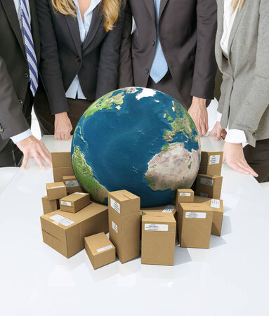 Meeting with people around a table with a world surrounded by cardboard boxes photo
