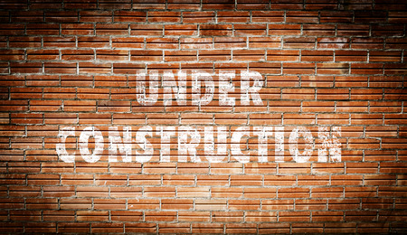 under construction sign: The words under construction written on a brick wall