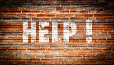 The word help written on a brick wall photo