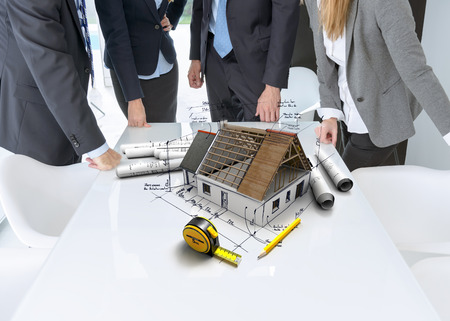 Meeting with people around a table with a residential architectural model with technical notes and details, blueprints and a tape measure photo