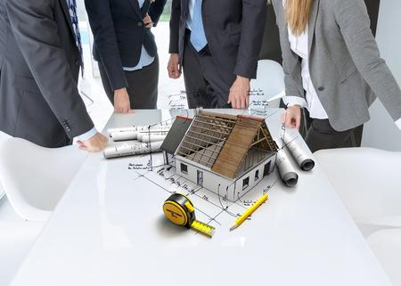 Treffen mit Menschen an einem Tisch mit einem Wohn-Architekturmodell mit technischen Hinweisen und Informationen, Blaupausen und einem Maßband Standard-Bild - 34416205