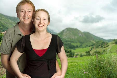Portrait of a happy couple against a green landscape photo