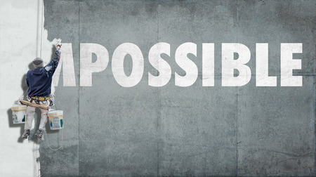 optimistic: Building painter overwriting the beginning of the word impossible so that it becomes possible Stock Photo