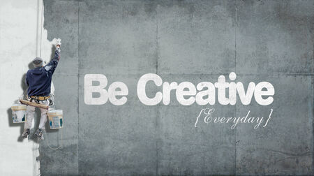 Painter hanging from harness painting a wall with the words be creative everyday photo