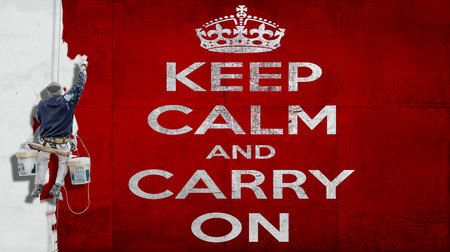 Building painter hanging from harness painting a red wall with white letters the motto Keep calm and carry on photo