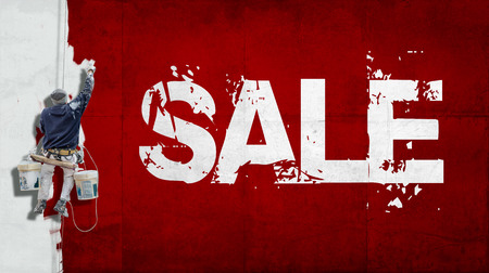 Painter hanging from harness painting a wall with the word sale photo