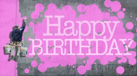 Painter hanging from harness painting a wall with the word Happy Birthday in pink photo