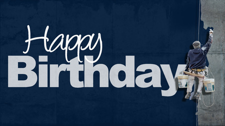 text word: Painter hanging from harness painting a wall with the word Happy Birthday in blue