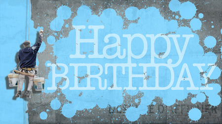 Painter hanging from harness painting a wall with the word Happy Birthday in blue photo