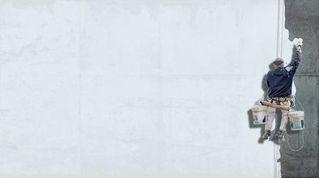 あなた自身のメッセージをコピー スペースの多くと白の壁を塗るハーネスからぶら下がっている画家を構築 写真素材