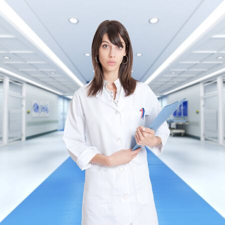 Young female professional holding a binder in a hospital corridor photo