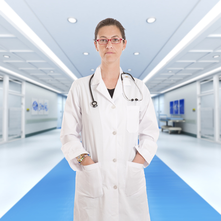 serious doctor: Serious female doctor standing at a hospital corridor Stock Photo