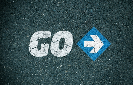 Road surface with the word go and an arrow sign Stock Photo