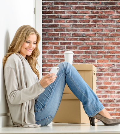Attractive young woman sitting on the floor with boxes checking her cell phone photo