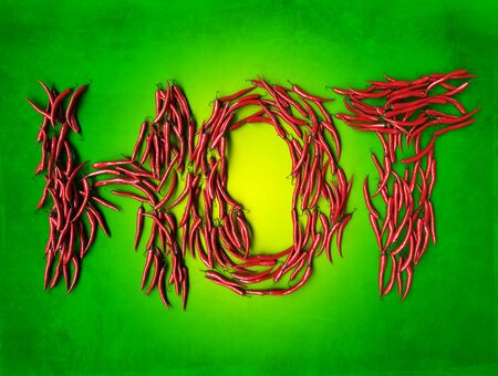 3D rendering of the word hot formed with chili peppers on a green backgrounds photo