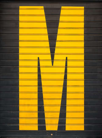 shut down: Painted yellow M letter on a black shop shutter Stock Photo