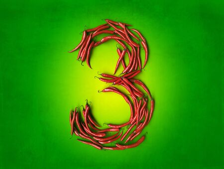cayenne: 3D rendering of number three formed with chili peppers on a green background Stock Photo