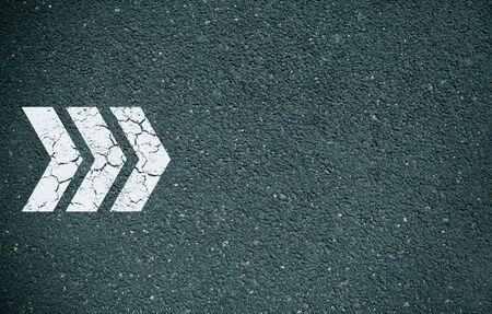 White arrow painted on tarmac