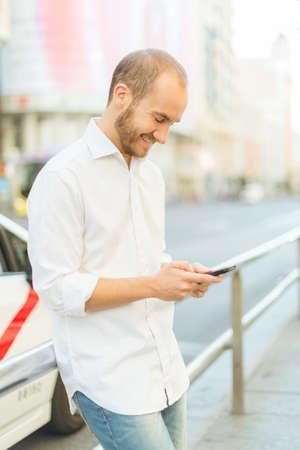 greeneyes: happy man texting on the street Stock Photo