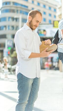 greeneyes: Man on the street checking a boot on a shoeshop Stock Photo