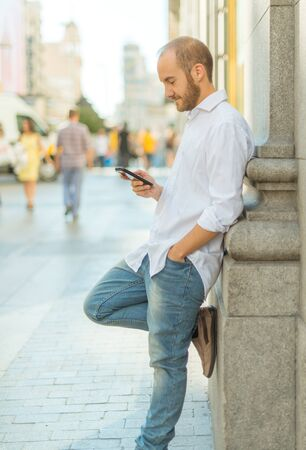 greeneyes: Young man leaning on a wall checking his phone Stock Photo