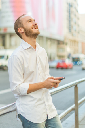 greeneyes: happy man texting on the street Stock Photo