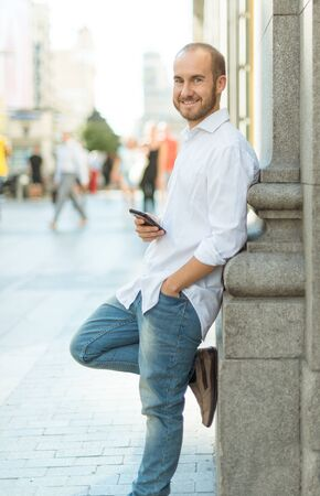 greeneyes: Happy man leaning on a wall in the street holding his phone Stock Photo