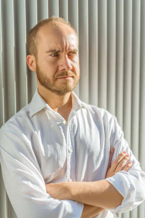 greeneyes: Serious looking man leaning against a corrugated iron wall Stock Photo