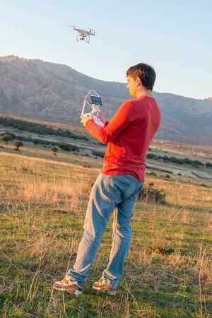 guiding: Man in a rural environment guiding a drone