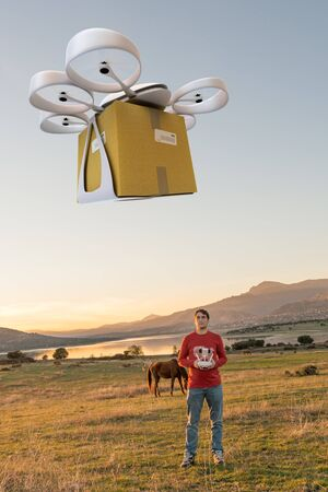 guiding: Man in a rural environment guiding a drone carrying a package