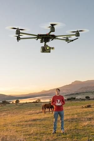 Man in a rural environment guiding a drone