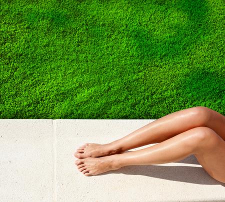 piernas mujer: Piernas de la mujer tomando el sol en el césped verde