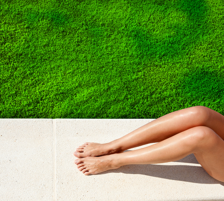 Woman legs sunbathing by green lawn Stockfoto
