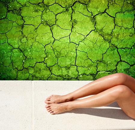 piernas mujer: tomar el sol piernas mujer tumbada en una tierra seca hasta Foto de archivo