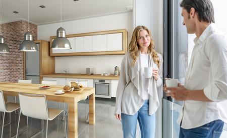 現代台所でコーヒーを飲む若いカップル 写真素材