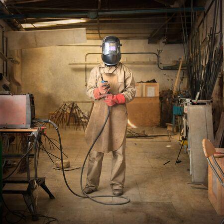 sculptor: Sculptor holding welder in a workshop