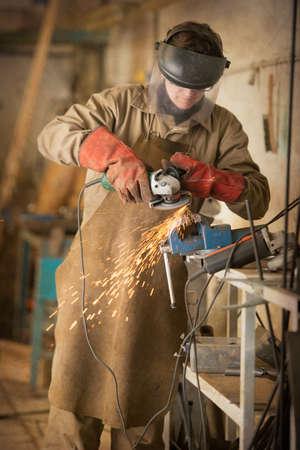 sculptor: Sculptor sawing metal with a circular saw Stock Photo